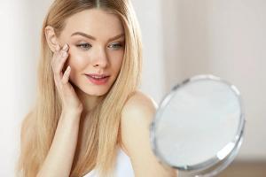 Девушка смотрится в зеркало