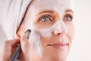 Женщина наносит маску на лицо