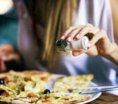 Девушка солит пиццу